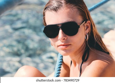Girl sitting on the pier wearing sunglasses
