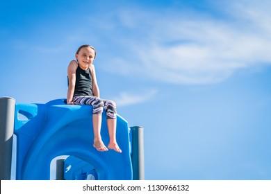 Girl sitting on playground equipment