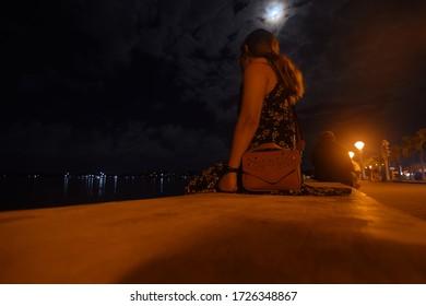 Girl sitting on Puerto Princesa Baywalk wall at night