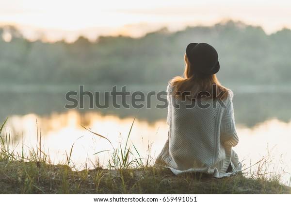 Ein Mädchen, das schweigend auf dem Flussufer saß
