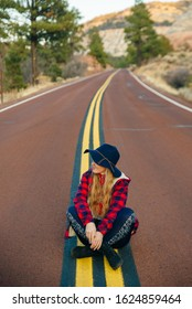 girl sitting on the road in Zion National Park in southwestern Utah near the town of Springdale