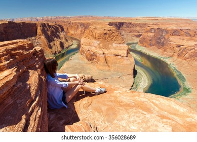 girl sitting on the rocks in front of Horseshoe Bend