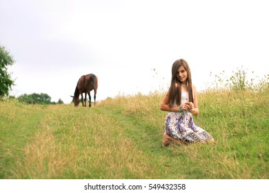 girl sitting on the rural road against a horse