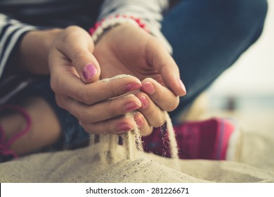 Girl sitting on sand at the beach. In her open palms sand that pours through her fingers. The girl dressed in jeans and pink sneakers, on her arms bracelets and a red manicure on nails. Vintage photo.