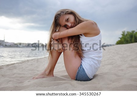 Long Naked girl sitting on beach