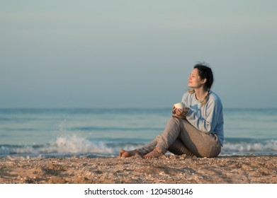 girl sitting on the sandy shore, the sea, cold, drink in the hands