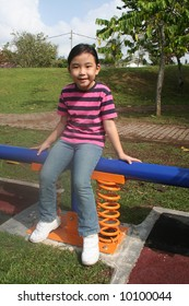 Girl sitting on the seesaw at the playground in the park
