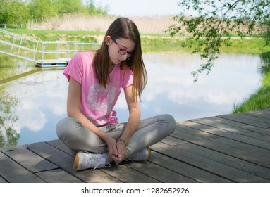 girl sitting on the shore of lake
