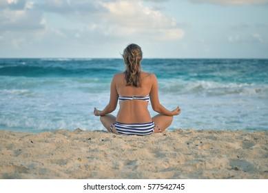 A girl sitting on the shore, Xcacel beach, Playa del Carmen, Mexico