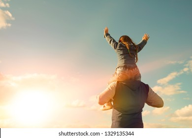 Girl sitting on the shoulders of a man against the sky. family value. family, relatives.