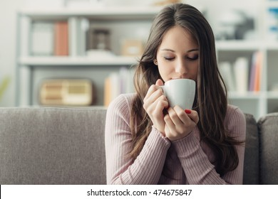 Girl sitting on the sofa at home and having a cup of coffee, relaxation concept