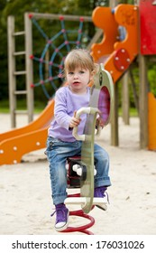 A girl sitting on a spring ride at the park.