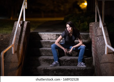 Girl sitting on steps at night looking out into the distance. Her lips are curved downward making her look slightly sad and depressed.