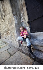 a girl sitting on steps on old wall background