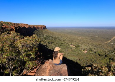 Girl sitting on stone on the cliff at an african landscape. Waterberg plateau, Namibia. Relax time on holiday concept travel.