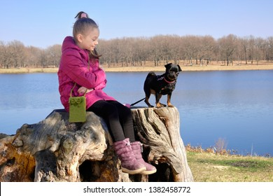 Girl sitting on a stump near the lake with a black dog PTI brabanson