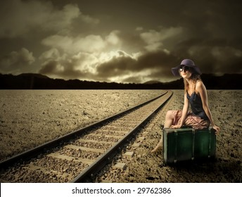girl sitting on a suitcase along the  train tracks