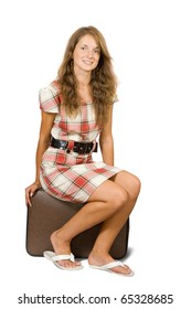 Girl sitting on suitcase. Isolated over white background