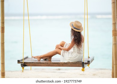 Girl sitting on a swing looking at the ocean
