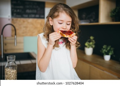 Girl sitting on the table in the kitchen and eating bread and jam