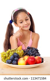 Girl sitting on the table with plate of fruit, isolated on white