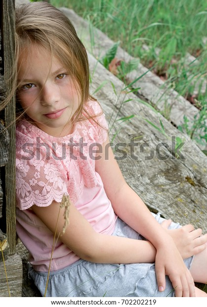 The girl is sitting on the threshold of an abandoned house