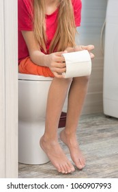 The girl is sitting on the toilet with a roll of toilet paper in hands