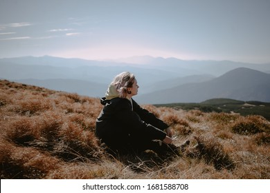 girl sitting on top and looking at the mountains