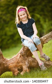 Girl sitting on a tree trunk at the golden hour on a warm summer day