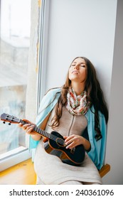 girl sitting on the window. playing guitar