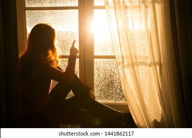 girl sitting on a windowsill and looking at the evening city at the beams of orange sunset sun