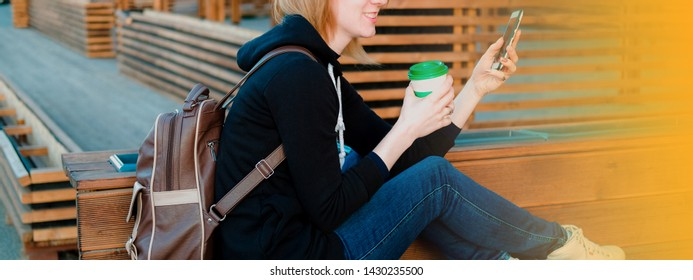 Girl sitting on wooden bench, holding paper cup of coffee and surfing the web with smartphone.