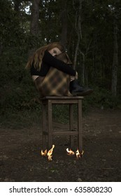 girl sitting on wooden chair on fire in the forest