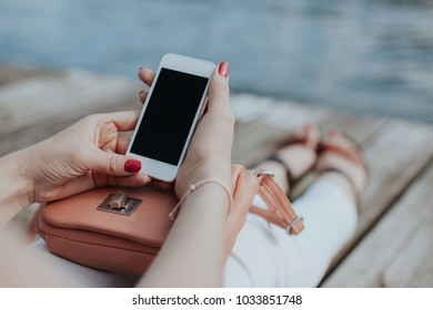 Girl sitting on wooden floor using white mobile phone. Vintage summer empty copy space background.