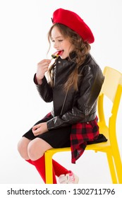 Girl sitting on a yellow chair and eating a lollipop. Cheerful and happy child.
