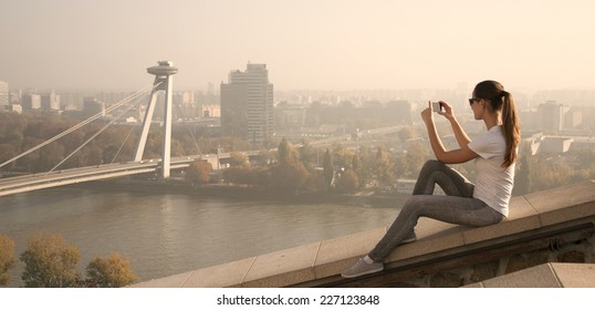 girl sitting over the city over the river and take pictures