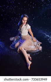 Girl sitting in the rain, night concept. Mystical style