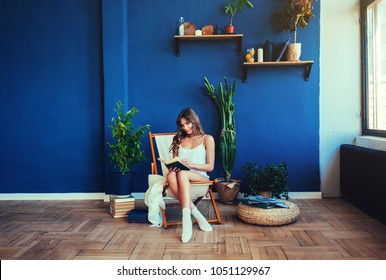 girl sitting and reading a book with a smile on a blue background
