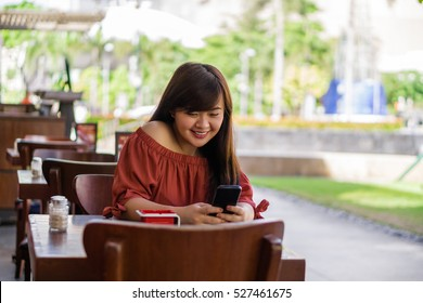 A girl sitting in a restaurant holding and looking at her phone