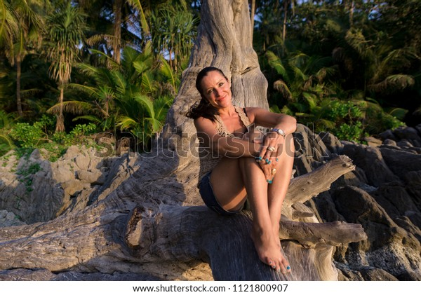 girl sitting smiling under a tree on the background of palm trees and other exotic plants