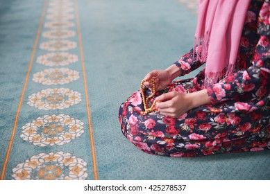 girl sitting sorts wooden beads in a mosque in floral dress, a Muslim