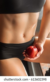 girl sitting in a sports trainer near the window. closeup of a stomach and a waist , in the hands of the red Apple