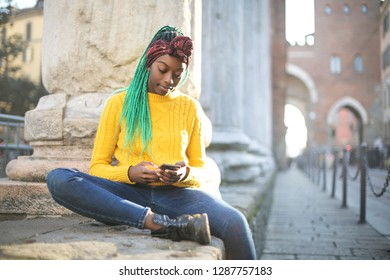 Girl sitting in the street, checking her phone