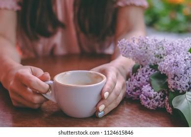 A girl is sitting at a table in cafe holding a cup with a drink. Copy space.