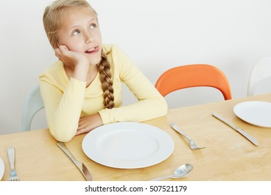 Girl sitting at table with empty plate, looking up
