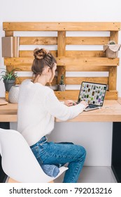 girl sitting at table with laptop with loaded pinterest page