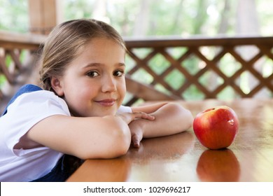 A girl is sitting at a table on which lies a red apple
