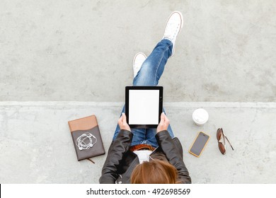 Girl sitting with a tablet in hands. Top view. Remote operation concept. Online education students. Online shopping