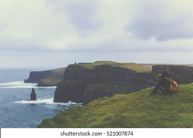 Girl sitting and thinking in the mountains in front of the sea in a cold day in Ireland
