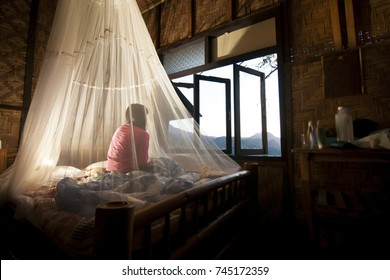 The girl sitting in the view,  in mosquito net at  room Made of bamboo.